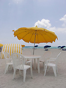 Plastic chairs with table and umbrellas Miami Beach USA