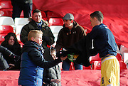 "Millwall's Shaun Williams hands a young fan a ""Kick It Out"" t-shirt before the Sky Bet Championship match between Nottingham Forest and Millwall at the City Ground, Nottingham, England on 31 January 2015. Photo by Jodie Minter."
