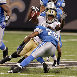 2009 September 13: New Orleans Saints running back Mike Bell (21) slips as Detroit Lions safety Louis Delmas (26) closes in during a 45-27 win by the New Orleans Saints over the Detroit Lions at the Louisiana Superdome in New Orleans, Louisiana.