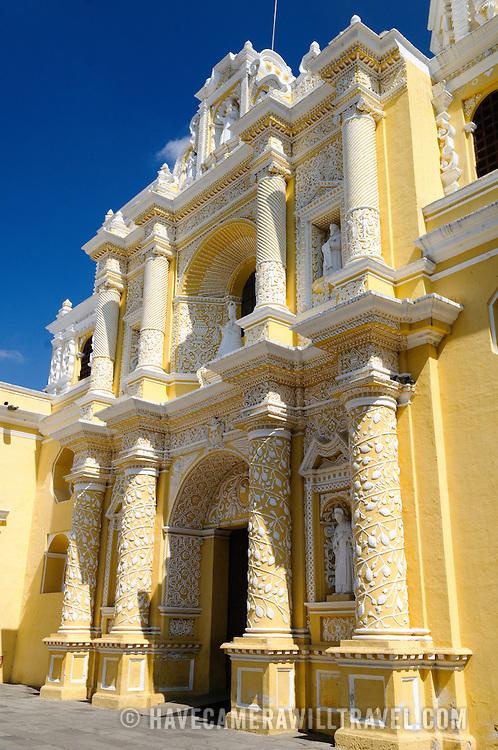 Front facade of the distinctive  and ornate yellow and white exterior of the Iglesia y Convento de Nuestra Senora de la Merced in downtown Antigua, Guatemala.