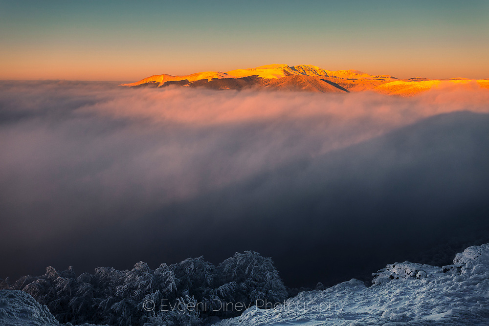 Red mountain peak above the clouds at sunrise