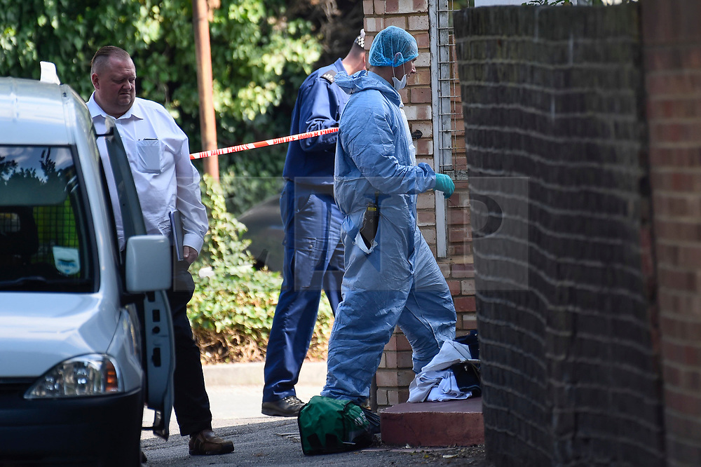 © Licensed to London News Pictures. 25/08/2019. SOUTHALL, UK.  A forensics officer enters a property adjacent to St Mary's Avenue near Southall in west London.  It is reported that a man in his 60s was stabbed outside The Plough pub on Tentelow Avenue in the early evening of 24 August and stumbled to nearby St Mary's Avenue to seek aid from a residence.  Police were called at 6.41pm, paramedics and air ambulance crews attended but the man passed away.  A man in his 30s has been arrested on suspicion of murder.  The investigation continues. Photo credit: Stephen Chung/LNP