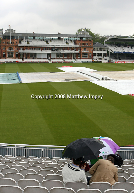 Spectators sit in the rain. England v New Zealand, Day 3, 1st Npower Test, Lord's Cricket Ground, St.Johns Wood, London,17/05/2008. © Matthew Impey / Wiredphotos.co.uk. tel: 07789 130 347 e: matt@wiredphotos.co.uk