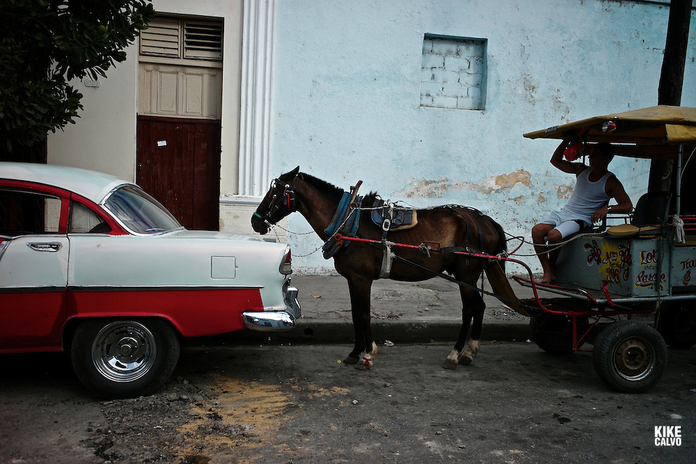 Horse carruage parked behind an old American car