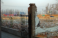 China, Beijing, Ping Fang Xiang, 2008. Alone amid demolished housing surrounding it a residence remain intact, the owner perhaps resisting offers to move elsewhere..