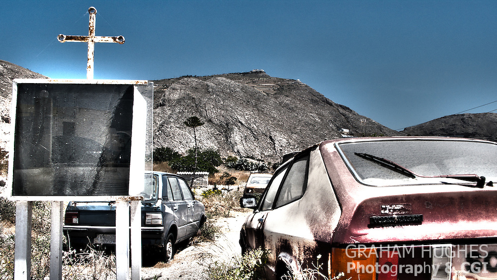 Old cars in scrap yard in Santorini, Greece. Cross of Church display board next to them.