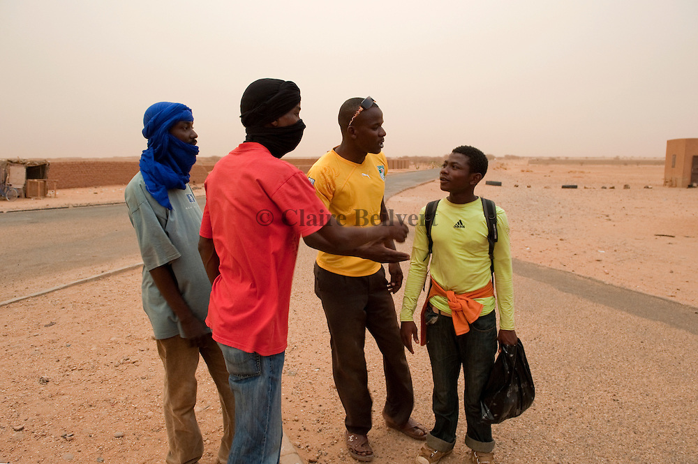 Niggerien touts in Agadez. They speak to a young african migrant. They try to convince him to come with them in Mohamed aka Boss' ghetto to organise his trip to Libya.