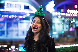"""© Licensed to London News Pictures . 16/12/2017. Manchester, UK. A woman wearing a Christmas tree hat at Deansgate Locks . Revellers out in Manchester City Centre overnight during """" Mad Friday """" , named for historically being one of the busiest nights of the year for the emergency services in the UK . Photo credit: Joel Goodman/LNP"""