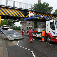 RTC on Tay Street, Perth.....19.07.10<br /> Recovery crews clear the remains of a lorry' s roof pictured on Tay Street in Perth after it collided with the railway bridge on the Perth to Dundee line ripping the roof of the lorry off and shedding its load. The road was closed as structural engineers checked the bridge.<br /> Picture by Graeme Hart.<br /> Copyright Perthshire Picture Agency<br /> Tel: 01738 623350  Mobile: 07990 594431