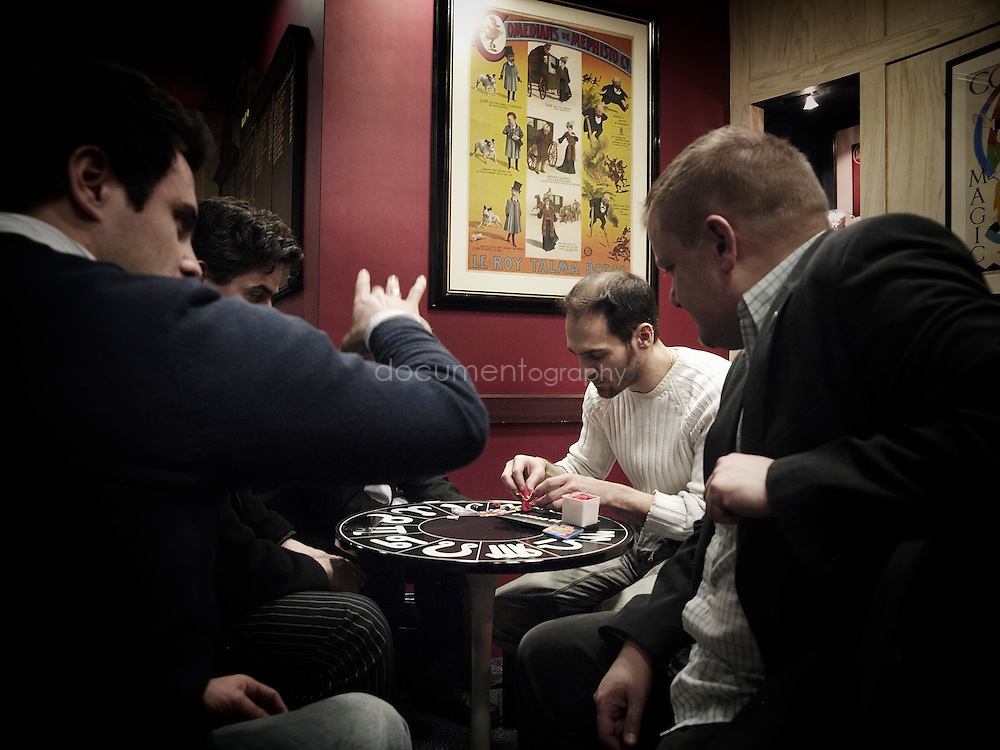 Leading magic inventor Angelo Carbone (centre in white) shows the latest trick he is developing to fellow members.  Carbone invented tricks for series such as 'Magicians' and 'The Sorcerer's Apprentice'.