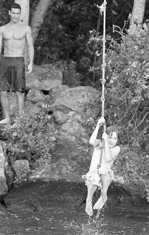 young boy on a lake rope swing while a good looking dad stands by watching from the shore
