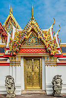 golden door and dragon statues at Wat Pho temple Bangkok Thailand