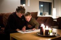 Amma Arndís og Ari Carl skoða myndaalbúm í Sandavaðinu. Grandma and grandson looking through a photo album at home. Candles on table.
