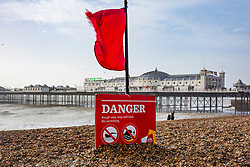 © Licensed to London News Pictures. 30/12/2017. Brighton, UK. A red flag and warning signs have been placed on the beach as powerful waves and strong gusts of wind are hitting Brighton and Hove. Photo credit: Hugo Michiels/LNP