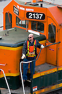 A BNSF Railway engineer controls his locomotive remotely with the beltpack system he is wearing around his waist. This locomotive is being used to switch the giant classification yard in Galesburg, IL.