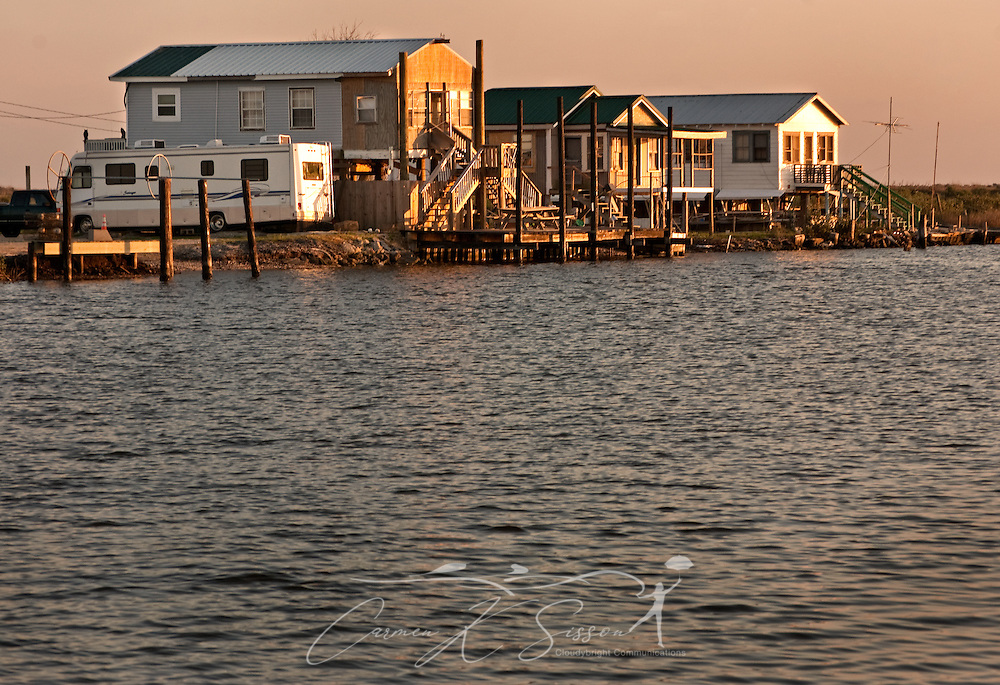 The sun sets on a trio of camps along Louisiana Highway 1 on March 6, 2011 in Grand Isle, La. The island was heavily impacted by the Deepwater Horizon oil spill April 20, 2010 and continues to recover. (Photo by Carmen K. Sisson)