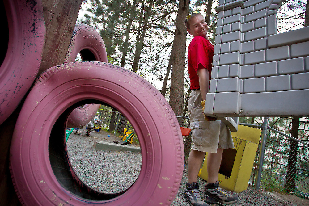 Jared Olbricht, with Keller Williams Realty Coeur d'Alene, carries out a discarded piece of playground equipment Thursday at the Little Folks Child Care.