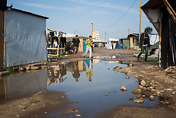 © Licensed to London News Pictures. 30/08/2015. Calais, France. People walk around puddles after last night's downpour at the refugee camp in Calais, also known as the Jungle. Tomorrow the French PM, Manuel Valls, will visit the day centre Jules Ferry at the camp. Photo credit : Isabel Infantes/LNP