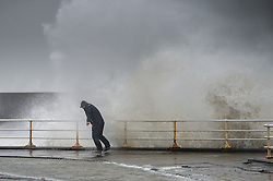 "© London News Pictures. 08/02/2014. Aberystwyth, UK. <br /> 43 year old RUSSEL THOMAS, from Worcester, attempts do dodge a huge wave as gale force winds strike the sea walls at Aberystwyth, Wales at high tide. The winds are forecast to strengthen throughout the day, gusting up to 70 or 80 mph, and with the rising tide, their impact could be potentially damaging again. An amber ""be prepared"" warning  has been issued by the Met Office for wind,. Photo credit: Keith Morris/LNP"