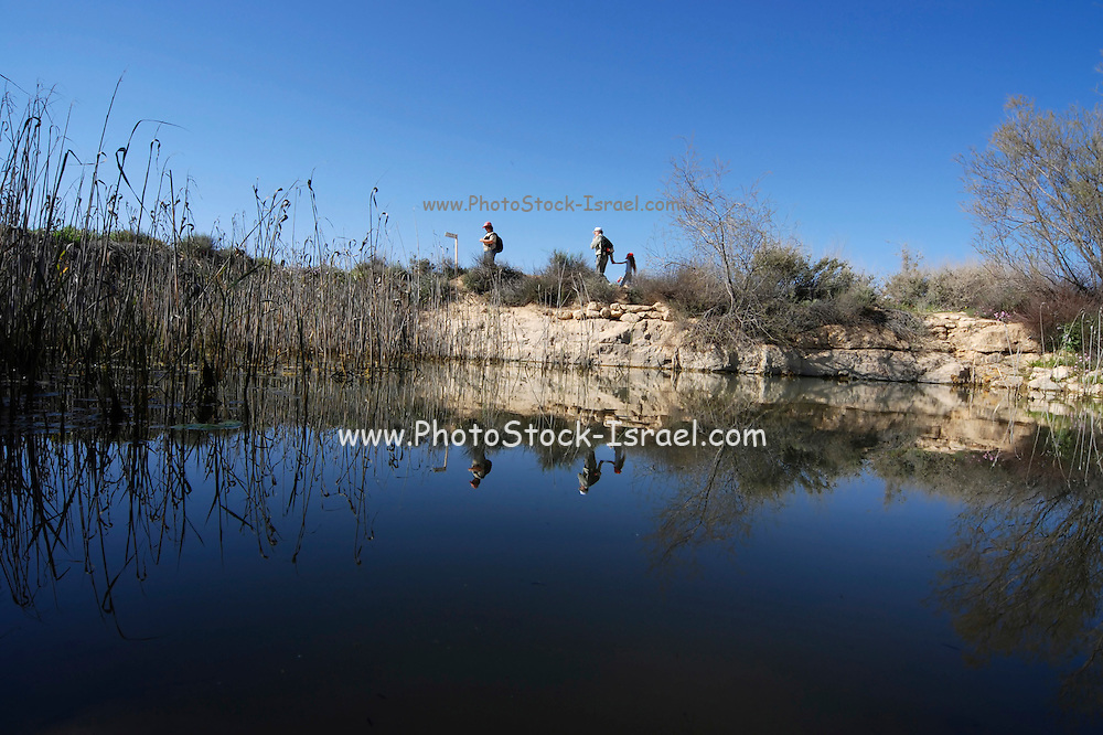 Israel, Negev, Borot Lotz, Lotz cisterns Hikers walking near the natural water pool in the nature preserve April 2007