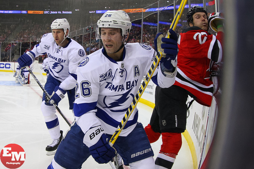 Feb 7, 2013; Newark, NJ, USA; Tampa Bay Lightning right wing Martin St. Louis (26) hits New Jersey Devils center David Clarkson (23) during the second period at the Prudential Center.