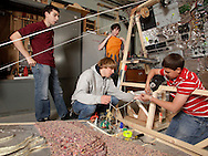 Pine Bush High School Odyssey of the Mind team members Dylan DiGasso, right, and Nic Besley, second front left, work on running string from a motor through a hook as Joe Landolino, left, looks on and Dan Stack holds a piece of material that will look like a flame when placed over a fan.