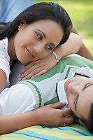 Couple lying down together on blanket in park