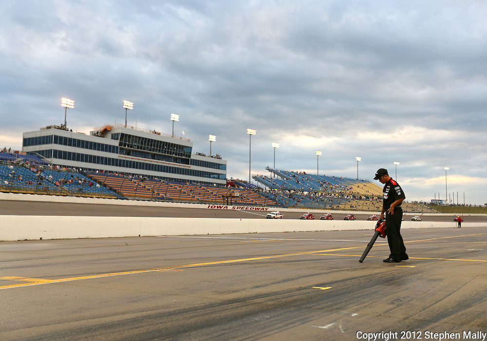 A worker dries off a pit spot before the start of the IZOD IndyCar Iowa Corn Indy 250 auto race at the Iowa Speedway in Newton, Iowa on Saturday, June 23, 2012.