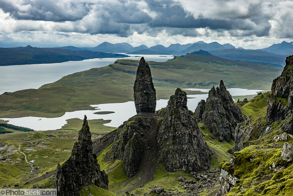 The Old Man of Storr rises above Loch Leathan, in the Trotternish area, Isle of Skye, Scotland, United Kingdom, Europe. On the horizon at upper left is Raasay Island surrounded by the Sound of Raasay, and at center are the Black Cuillins mountains. A massive ancient landside created this distinctive landscape of eroded pinnacles.