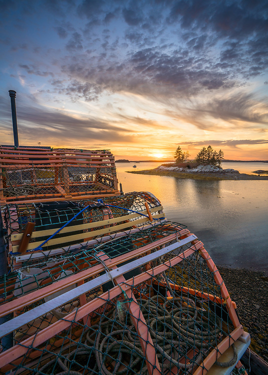 These old traps are stacked along the shoreline at Lookout Point in Harpswell. You can see a small island offshore in front of a beautiful sunset.