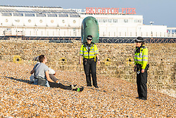 © Licensed to London News Pictures.08/04/2020. Brighton, UK. Members of the public enjoy the warmer weather by relaxing on the beach and taking a walk on the Brighton and Hove promenade as police continues to advise people of the Coronavirus lockdown laws. Photo credit: Hugo Michiels/LNP