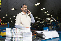 Man using telephone in factory with newspapers