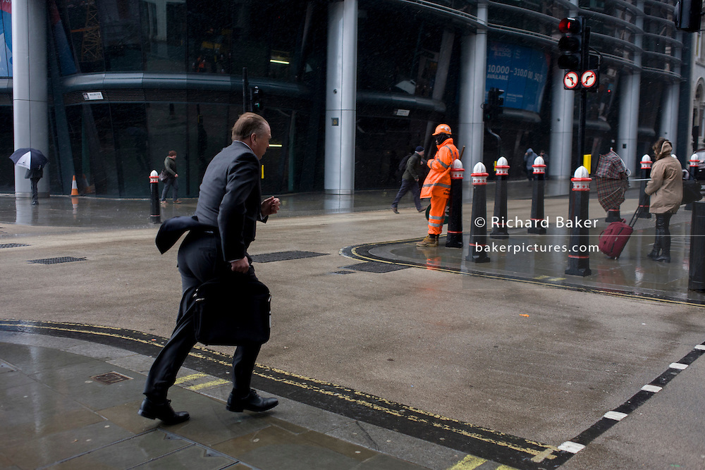 Londoners have their umbrellas turned inside out or dash through seasonal rain showers and wind gusts in central London.