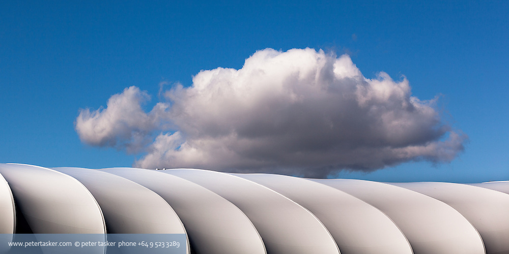 A single cloud hovering over the roof of Queens Wharf 2011 Rugby World Cup structure named The Cloud.
