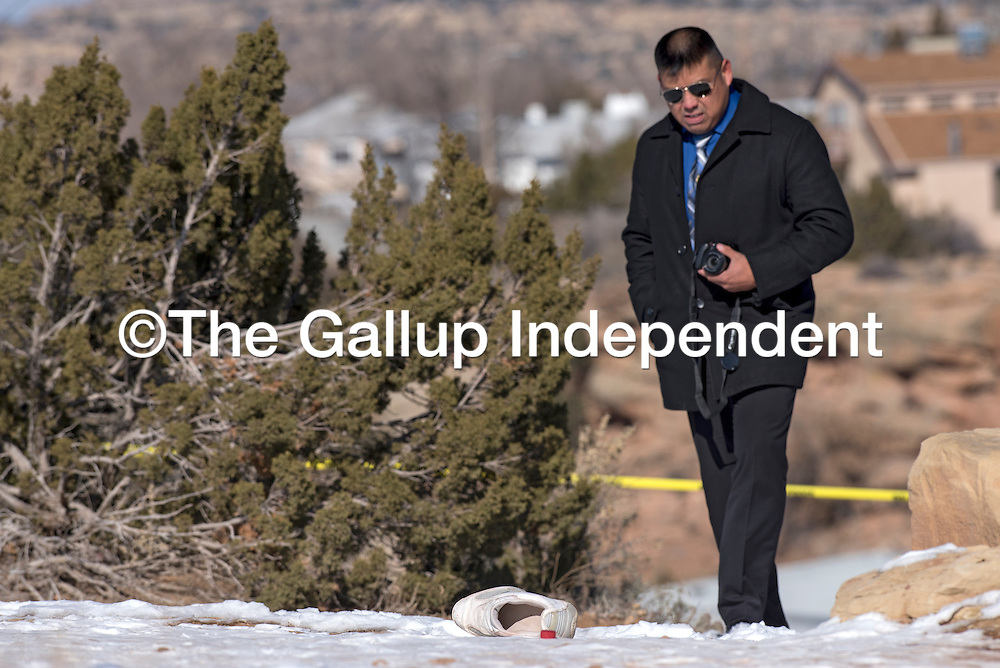 123114       Adron Gardner<br /> <br /> Detective Mark Spencer examines the scene of a body found near Sundance Dental on North 2nd Street in Gallup Wednesday.