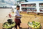 "17 JUNE 2013 - YANGON, MYANMAR:  A fruit vendor watches a Yangon bound ferry pull away from the dock in Dala. The ferry to Dala opposite Yangon on the Yangon River is the main form of transportation across the river. Every day the ferry moves tens of thousands of people across the river. Many working class Burmese live in Dala and work in Yangon. The ferry is also popular with tourists who want to experience the ""real"" Myanmar. The rides takes about 15 minutes. Burmese pay about the equivalent of .06¢ US for a ticket.  Foreigners pay about the equivalent of about $4.50 US for the same ticket.   PHOTO BY JACK KURTZ"