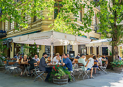 Busy cafe on pavement in summer in Prenzlauer Berg district of Berlin Germany