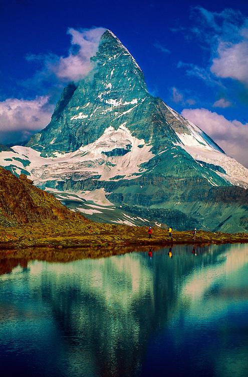 Hikers pass behind the Riffelsee with the Matterhorn behind, Zermatt, Switzerland.
