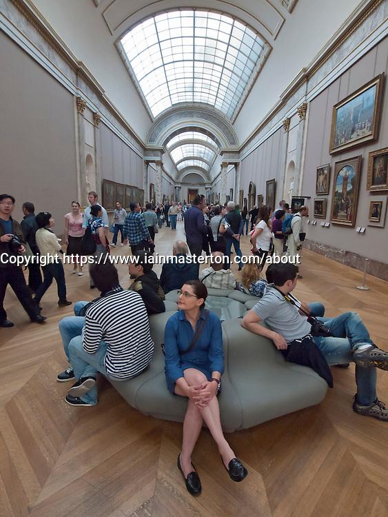 Interior of corridor full of tourists in The Louvre museum in Paris France