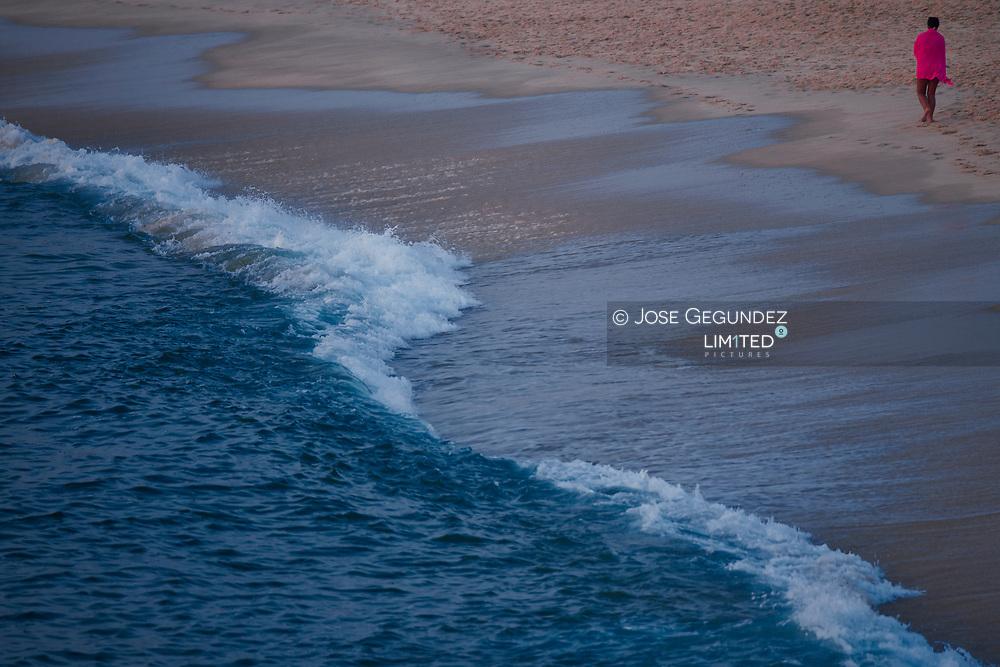 Woman wear a fuchsia towel walking on the beach