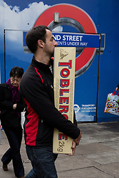 © Licensed to London News Pictures. 13/12/2015. London, UK. A man walks down Oxford Street with a giant 2kg Toblerone chocolate on the penultimate shopping weekend before Christmas.  Photo credit : Vickie Flores/LNP