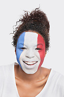 Portrait of happy young African American woman with French flag painted on face against white background