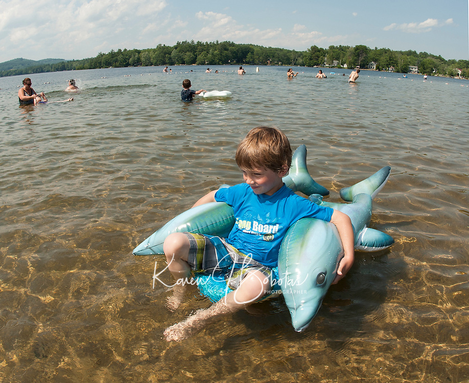 Evan Tucker and his twin dolphins enjoy a perfect summer's day at the Waukewan Beach on Friday afternoon.  (Karen Bobotas/for the Laconia Daily Sun)