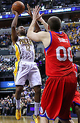 March 14, 2012; Indianapolis, IN, USA; Indiana Pacers guard A.J. Price (12) shoots against Philadelphia 76ers center Spencer Hawes (0) at Bankers Life Fieldhouse. Indiana defeated Philadelphia 111-94. Mandatory credit: Michael Hickey-US PRESSWIRE
