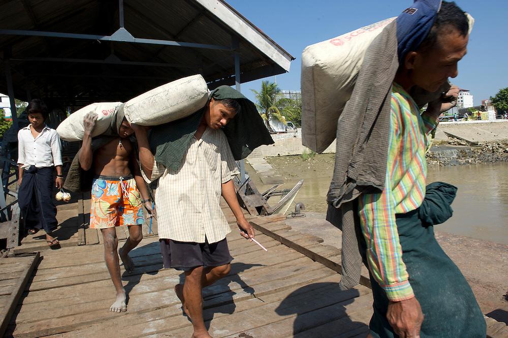 Men carry goods onto boats at Yangon's Port. Yangon (Rangoon) Myanmar (Burma) January 2012