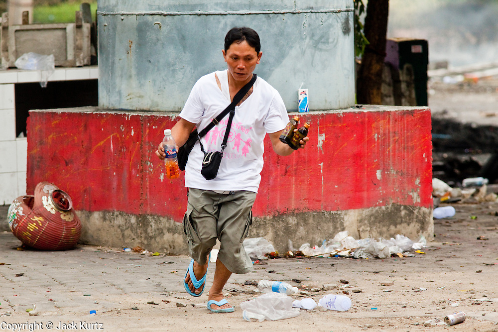 18 MAY 2010 - BANGKOK, THAILAND: A man runs to cover with petrol bombs at Din Daeng Intersection in Bangkok Tuesday. The intersection has been under periodic sniper fire from unidentified snipers near Thai military lines. Violent unrest continued in Bangkok again Tuesday nearly a week after Thai troops started firing on protesters and Bangkok residents took to the streets in violent protest against the government. Tuesday was not as violent as previous days however. Although protesters continued to set up roadblocks and flaming tire barricades across parts of the city, there was not as much gunfire from the government lines. The most active protesters were at the Din Daeng Intersection about a mile from the Red Shirts' Ratchaprasong camp.  PHOTO BY JACK KURTZ