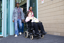 Group of friends; including a young woman who is a wheelchair user; leaving a public building together,