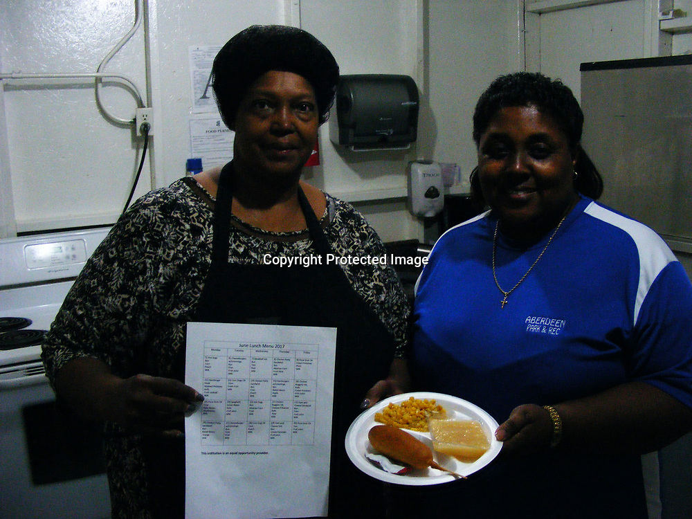 Sandra Walker, left, holds a copy of the menu she devised for the Aberdeen Park and Recreation Department's summer program while Tohona Larthridge holds plate of corn dogs, fruit and corn served during the program. Walker's training in school food service has helped her prepare menus and food for large groups.