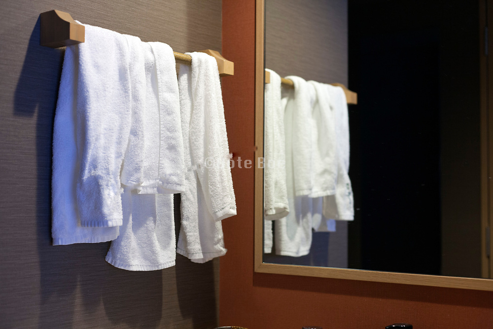 used bathroom towels on rack with mirror reflection