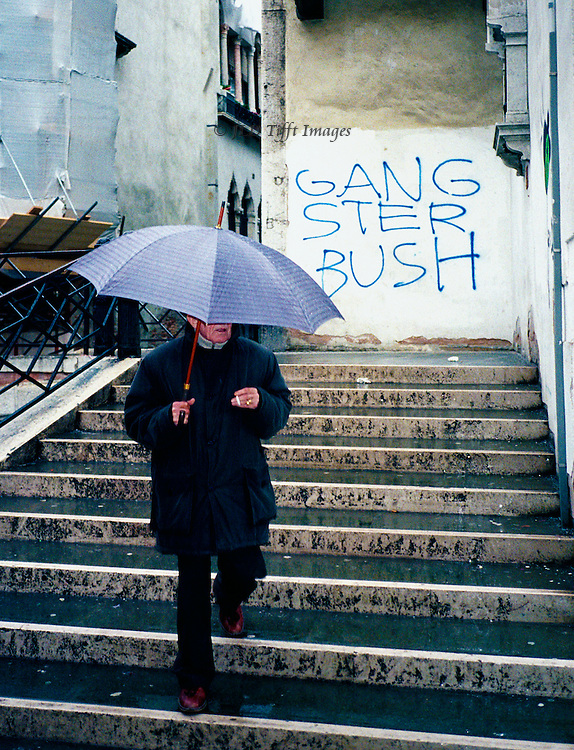 "Graffiti: ""Gangster Bush"" on a bridge in Venice, pedestrian holding up an umbrella in one hand and a cigarette in the other, descends the stairs off the bridge, on a rainy day..."